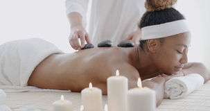 Woman Getting Hot Stone Massage. Young woman getting hot stone massage in spa salon Stock Photo