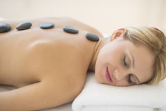 Woman Getting Hot Stone Therapy At Health Spa. Relaxed young woman getting hot stone therapy at health spa Royalty Free Stock Photography