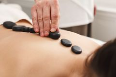 Woman getting hot stones massage at spa salon. Beautiful woman getting hot stones back massage in spa salon. Beauty treatment therapy, wellness and relaxation Stock Photos