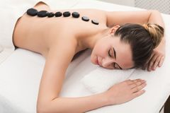 Woman getting hot stones massage at spa salon. Beautiful woman at hot stones massage in spa salon. Beauty treatment therapy, wellness and relaxation concept Royalty Free Stock Images