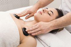 Woman getting hot stones massage at spa salon. Beautiful woman getting hot stones shoulders massage in spa salon. Beauty treatment therapy, wellness and Royalty Free Stock Photography