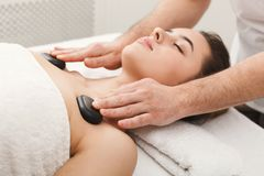 Woman getting hot stones massage at spa salon. Beautiful woman getting hot stones shoulders massage in spa salon. Beauty treatment therapy, wellness and Stock Images