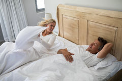 Woman getting irritated while man snoring on bed. Woman getting irritated while men snoring on bed in bedroom Royalty Free Stock Image