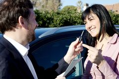 Woman getting keys of new car from salesman Royalty Free Stock Photos