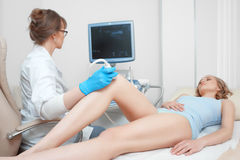 Woman getting knee ultrasound scanning examination at the clinic royalty free stock photography