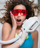 Woman getting laser face treatment in medical spa center. Funny expression, hesitation, pain concept Royalty Free Stock Photos