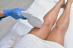 Woman getting legs skin laser treatment in a beauty salon, close. Up royalty free stock photography