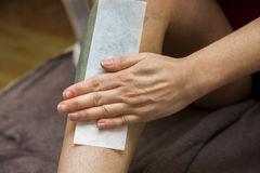 Woman getting legs waxed for hair removal in home Stock Image