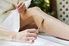 Woman getting legs waxed at a spa royalty free stock photography