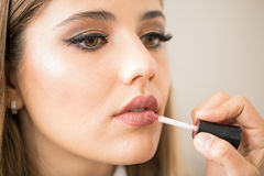 Woman getting lipstick on her lips royalty free stock photography