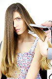 Woman getting long hair straightened with iron Royalty Free Stock Images