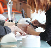 Woman getting manicure at beauty salon Stock Photos