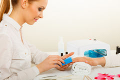 Woman getting manicure done file nails Royalty Free Stock Image