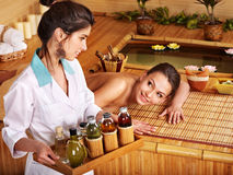 Woman getting massage in bamboo spa. Young woman getting massage in bamboo spa Stock Images