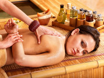 Woman getting massage in bamboo spa. Royalty Free Stock Image