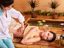 Woman getting massage in bamboo spa. Royalty Free Stock Photo