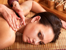 Woman getting massage in bamboo spa. Stock Images