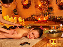 Woman getting massage in bamboo spa. Young woman getting massage in bamboo spa with burning candles royalty free stock image