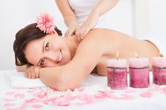 Woman Getting Massage Treatment. Smiling Young Woman Getting Massage Treatment From Masseuse Stock Photo