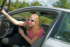 Woman getting out of car. A view of a pretty young blond woman wearing sun glasses getting out of a car Stock Photography
