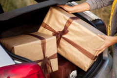 Woman getting out of her car with presents Stock Image