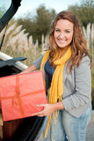Woman getting out of her car with presents Royalty Free Stock Images
