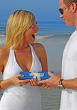 Woman getting present. Excited woman receiving present on beach Stock Photography
