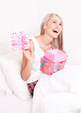 Woman getting presents. Beautiful young blond woman wakes up and finds on the bed at home stock photo