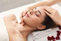 Woman getting professional facial massage at spa. Woman enjoying anti aging facial massage, lying on table with rose petals. Pretty girl getting professional stock images