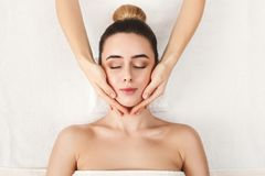 Woman getting professional facial massage at spa. Facial massage. Spa, resort, beauty and health concept. Beautiful woman getting professional face treatment stock photography