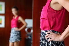 Woman trying clothing looking at the mirror stock images