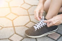 Woman getting ready to run and tying running shoes stock photography