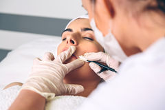 Woman getting rf lifting in her face in clinic Stock Photo