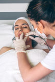 Woman getting rf lifting in her face in clinic Royalty Free Stock Images