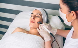 Woman getting rf lifting in her face in clinic Stock Images