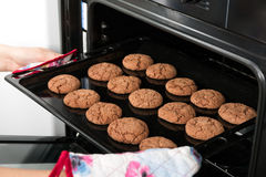 Woman getting roasting pan with oat cookies Stock Images