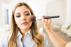 Woman getting some blush in a salon. Portrait of a beautiful young women getting some blush and makeup on in a beauty studio Stock Photos