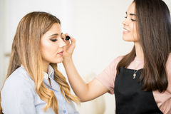 Woman getting some mascara on. Profile view of a cute makeup artist putting some mascara on a women in a beauty salton Stock Photography