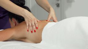 Woman getting soothing massage at the hands of a professional masseuse. Sliding cropped shot of a professional masseuse working, doing massage. Woman enjoying stock photos