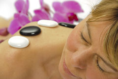 Spa massage. Woman getting spa with massage stones and orchid flower royalty free stock photos