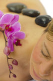 Spa massage. Woman getting spa with massage stones and orchid flower stock photography