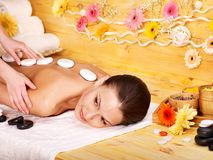 Woman getting stone therapy massage . Woman getting stone therapy massage in wooden spa Royalty Free Stock Photos