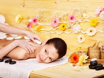 Woman getting stone therapy massage . Happy woman getting stone therapy massage in spa Royalty Free Stock Photos