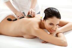 Woman Getting Stones Massage in Spa Salon. Spa Tretment. Beautiful Woman Getting Spa Hot Stones Massage in Spa Salon Stock Images