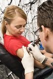 Woman getting tattoo. Royalty Free Stock Photos