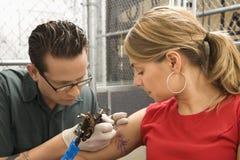 Woman getting tattoo. Caucasian male tattoo artist tattooing Caucasian woman Stock Image