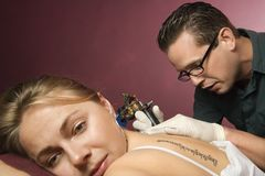 Woman getting tattooed. Stock Image