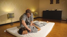 Woman getting thai herbal compress massage in spa stock video