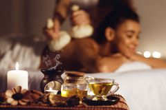 Woman getting thai herbal compress massage in spa. With aroma candles on foreground stock photo