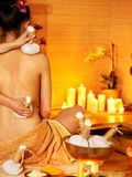 Woman getting thai herbal massage ball. Royalty Free Stock Photography